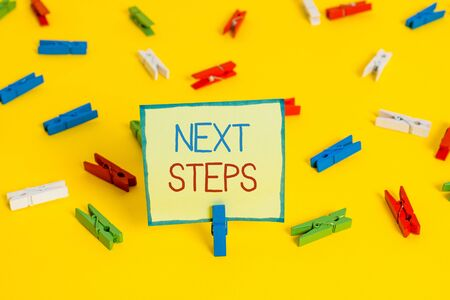 Text sign showing Next Steps. Business photo text something you do or plan after you ve finished something else Colored clothespin papers empty reminder yellow floor background office Zdjęcie Seryjne