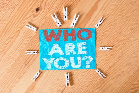 Word writing text Who Are You Question. Business photo showcasing asking about someone identity or demonstratingal information Colored clothespin papers empty reminder wooden floor background office
