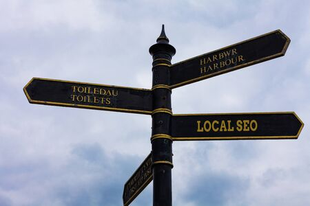 Word writing text Local Seo. Business photo showcasing helps businesses promote products and services to local customers Road sign on the crossroads with blue cloudy sky in the background