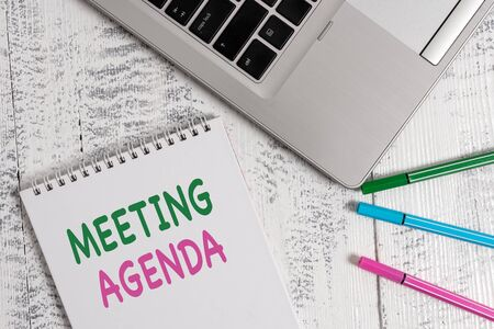 Word writing text Meeting Agenda. Business photo showcasing items that participants hope to accomplish at a meeting Top trendy metallic laptop blank spiral notepad pens lying wooden table Zdjęcie Seryjne