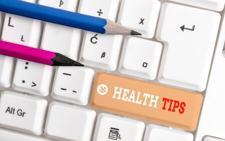 Word writing text Health Tips. Business photo showcasing advice or information given to be helpful in being healthy White pc keyboard with empty note paper above white background key copy space