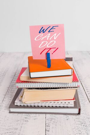 Handwriting text We Can Do It. Conceptual photo see yourself as powerful capable demonstrating pile stacked books notebook pin clothespin colored reminder white wooden Zdjęcie Seryjne