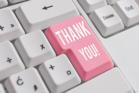 Conceptual hand writing showing Thank You. Concept meaning polite expression used when acknowledging gift service compliment White pc keyboard with note paper above the white background Zdjęcie Seryjne