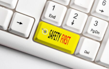 Conceptual hand writing showing Safety First. Concept meaning used to say that the most important thing is to be safe White pc keyboard with note paper above the white background