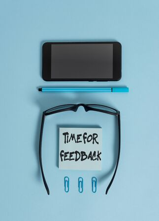 Writing note showing Time For Feedback. Business concept for information about reactions to a product or services Dark eyeglasses colored sticky note smartphone pen pastel background Zdjęcie Seryjne