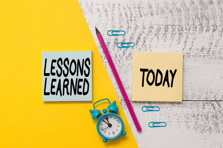 Word writing text Lessons Learned. Business photo showcasing the knowledge or understanding gained by experience Notepads marker pen colored paper sheet alarm clock wooden background 版權商用圖片