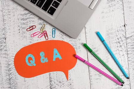 Handwriting text Q And A. Conceptual photo a period of time or an occasion when someone answers questions Trendy metallic laptop speech bubble colored clips pens lying vintage table Stock Photo