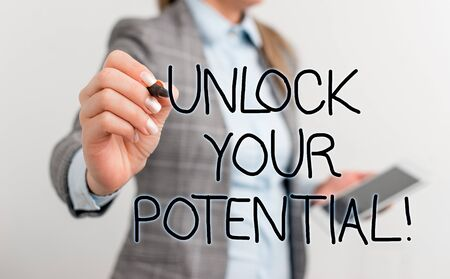 Text sign showing Unlock Your Potential. Business photo text release possibilities Education and good training is key Business woman pointing in empty space with pen and mobile phone Stockfoto - 129237602