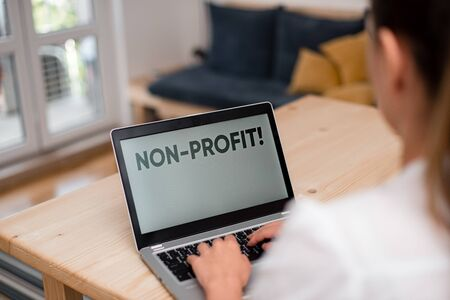 Conceptual hand writing showing NonProfit. Concept meaning not making or conducted primarily to make profit organization woman with laptop smartphone and office supplies technology