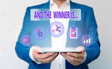 Word writing text And The Winner Is. Business photo showcasing announcing a demonstrating or thing that wins something Male human wear formal work suit presenting presentation using smart device