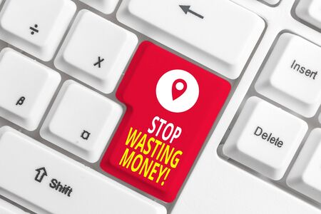 Writing note showing Stop Wasting Money. Business concept for advicing demonstrating or group to start saving and use it wisely White pc keyboard with note paper above the white background 写真素材
