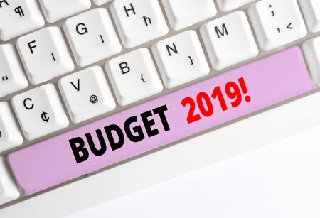 Handwriting text writing Budget 2019. Conceptual photo the estimate of income and expenditure for current year White pc keyboard with empty note paper above white background key copy space Stok Fotoğraf