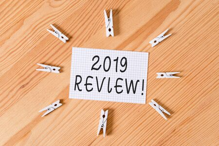 Conceptual hand writing showing 2019 Review. Concept meaning remembering past year events main actions or good shows Colored crumpled papers wooden floor background clothespin