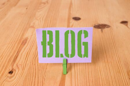 Writing note showing Blogquestion. Business concept for regularly updated website web page run by individual Wooden floor background green clothespin groove slot office