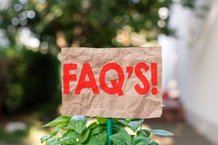 Word writing text Faq S. Business photo showcasing list of questions and answers relating to particular subject Plain empty paper attached to a stick and placed in the green leafy plants