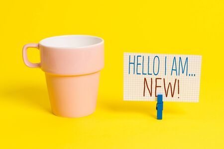 Word writing text Hello I Am New. Business photo showcasing used as greeting or to begin telephone conversation Cup empty paper blue clothespin rectangle shaped reminder yellow office
