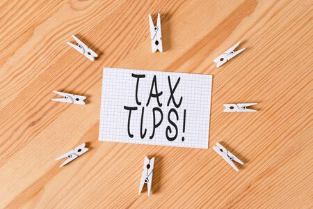 Conceptual hand writing showing Tax Tips. Concept meaning compulsory contribution to state revenue levied by government Colored crumpled papers wooden floor background clothespin Banco de Imagens