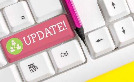 Text sign showing UPDATE. Business photo showcasing make something more modern or up to date like software program White pc keyboard with empty note paper above white background key copy space