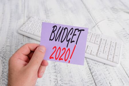 Text sign showing Budget 2020. Business photo showcasing estimate of income and expenditure for next or current year man holding colorful reminder square shaped paper white keyboard wood floor Banco de Imagens