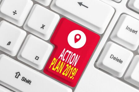 Writing note showing Action Plan 2019. Business concept for proposed strategy or course of actions for current year White pc keyboard with note paper above the white background Banco de Imagens