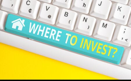 Text sign showing Where To Invest question. Business photo showcasing asking about actions or process of making more money White pc keyboard with empty note paper above white background key copy space