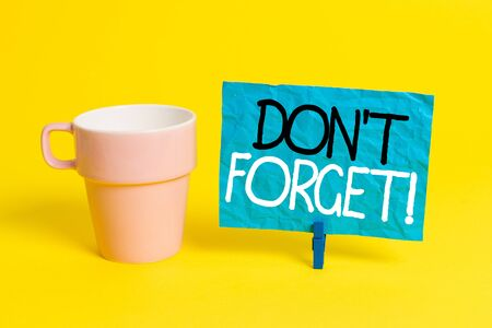 Handwriting text Don T Forget. Conceptual photo used to remind someone about important fact or detail Cup empty paper blue clothespin rectangle shaped reminder yellow office