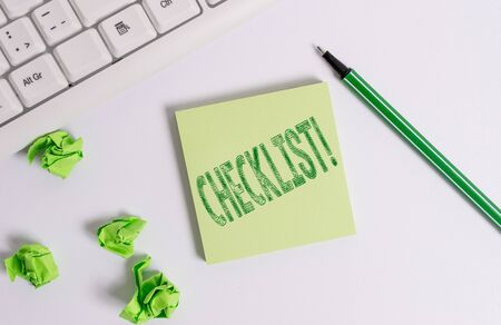 Conceptual hand writing showing Checklist. Concept meaning list items required things be done or points considered Green note paper with pencil on white background and pc keyboard