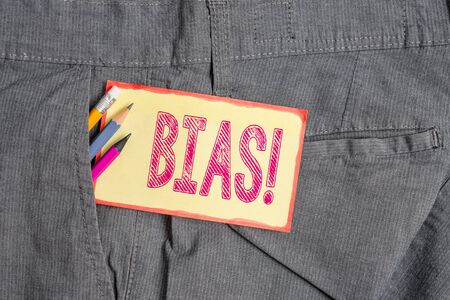 Conceptual hand writing showing Bias. Concept meaning inclination or prejudice for or against one demonstrating group Writing equipment and yellow notepaper in pocket of trousers