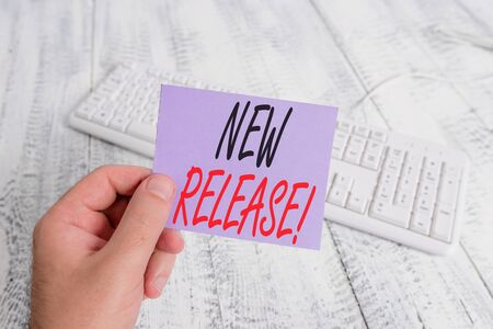 Text sign showing New Release. Business photo showcasing announcing something newsworthy recent product man holding colorful reminder square shaped paper white keyboard wood floor Foto de archivo - 129286499