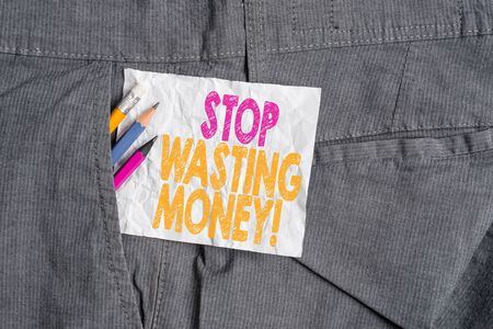Text sign showing Stop Wasting Money. Business photo showcasing advicing demonstrating or group to start saving and use it wisely Writing equipment and white note paper inside pocket of man work trousers Stock fotó - 129287096