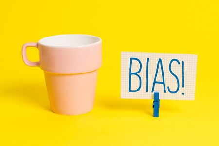 Word writing text Bias. Business photo showcasing inclination or prejudice for or against one demonstrating group Cup empty paper blue clothespin rectangle shaped reminder yellow office