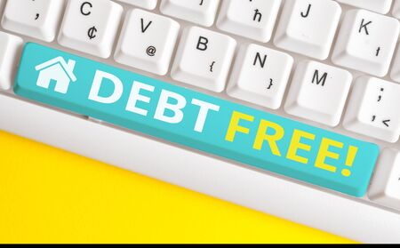 Text sign showing Debt Free. Business photo showcasing does not owning any money to any individual or companies White pc keyboard with empty note paper above white background key copy space