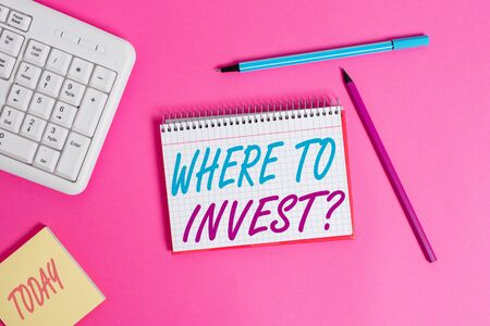 Conceptual hand writing showing Where To Invest question. Concept meaning asking about actions or process of making more money Writing equipments and computer stuff placed on wooden table