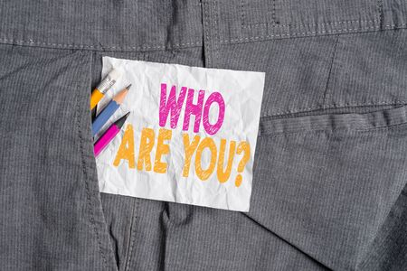Text sign showing Who Are You Question. Business photo showcasing asking about someone identity or demonstratingal information Writing equipment and white note paper inside pocket of man work trousers