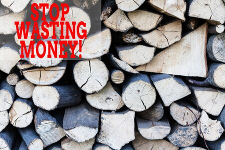 Text sign showing Stop Wasting Money. Business photo showcasing advicing demonstrating or group to start saving and use it wisely Background dry chopped firewood logs stacked up in a pile winter chimney