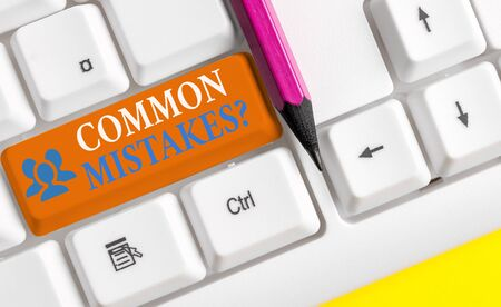 Writing note showing Common Mistakes question. Business concept for repeat act or judgement misguided or wrong White pc keyboard with note paper above the white background
