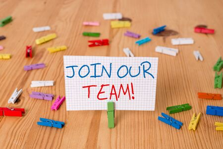Text sign showing Join Our Team. Business photo text inviting someone into your local group or company Colored clothespin papers empty reminder wooden floor background office
