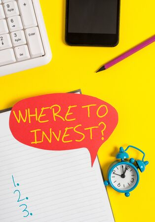 Text sign showing Where To Invest question. Business photo showcasing asking about actions or process of making more money Empty red bubble paper on the table with pc keyboard