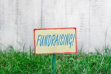 Writing note showing Fundraising. Business concept for seeking to generate financial support for charity or cause Plain paper attached to stick and placed in the grassy land