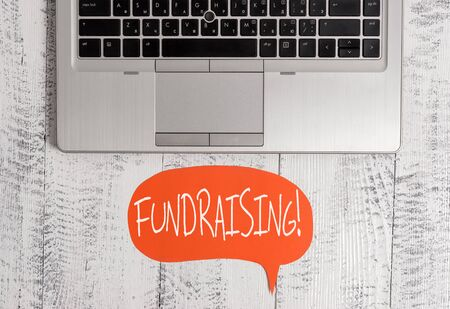 Writing note showing Fundraising. Business concept for seeking to generate financial support for charity or cause Close view open laptop speech bubble downwards lying vintage table Stok Fotoğraf