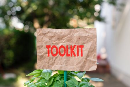 Word writing text Toolkit. Business photo showcasing set of tools kept in a bag or box and used for a particular purpose Plain empty paper attached to a stick and placed in the green leafy plants