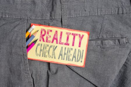 Conceptual hand writing showing Reality Check Ahead. Concept meaning makes them recognize truth about situations or difficulties Writing equipment and yellow notepaper in pocket of trousers