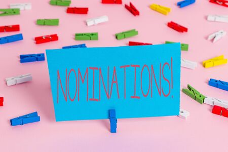 Writing note showing Nominations. Business concept for action of nominating or state being nominated for prize Colored clothespin papers empty reminder pink floor office pin