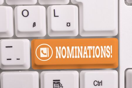 Writing note showing Nominations. Business concept for action of nominating or state being nominated for prize White pc keyboard with note paper above the white background Archivio Fotografico