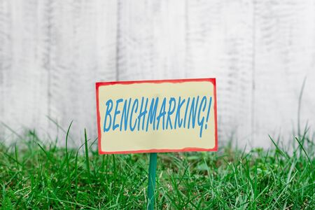 Writing note showing Benchmarking. Business concept for evaluate something by comparison with standard or scores Plain paper attached to stick and placed in the grassy land