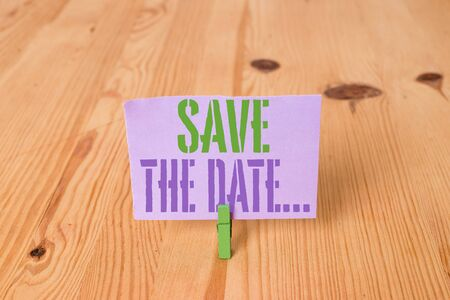 Writing note showing Save The Date. Business concept for Organizing events well make day special event organizers Wooden floor background green clothespin groove slot office Stockfoto