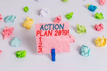 Conceptual hand writing showing Action Plan 2019. Concept meaning proposed strategy or course of actions for current year Colored crumpled paper empty reminder white floor clothespin