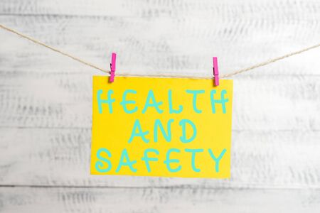 Conceptual hand writing showing Health And Safety question. Concept meaning regulations and procedures intended to prevent accident Clothespin rectangle shaped paper reminder white wood desk