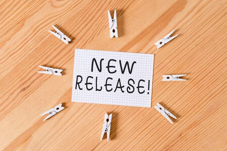 Conceptual hand writing showing New Release. Concept meaning announcing something newsworthy recent product Colored crumpled papers wooden floor background clothespin