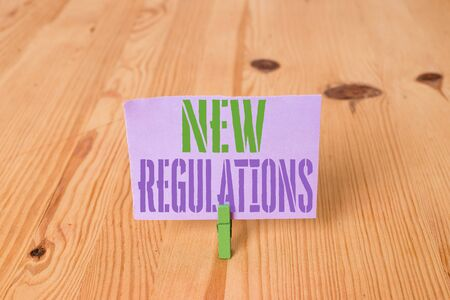 Writing note showing New Regulations question. Business concept for rules made government order to control way something is done Wooden floor background green clothespin groove slot office
